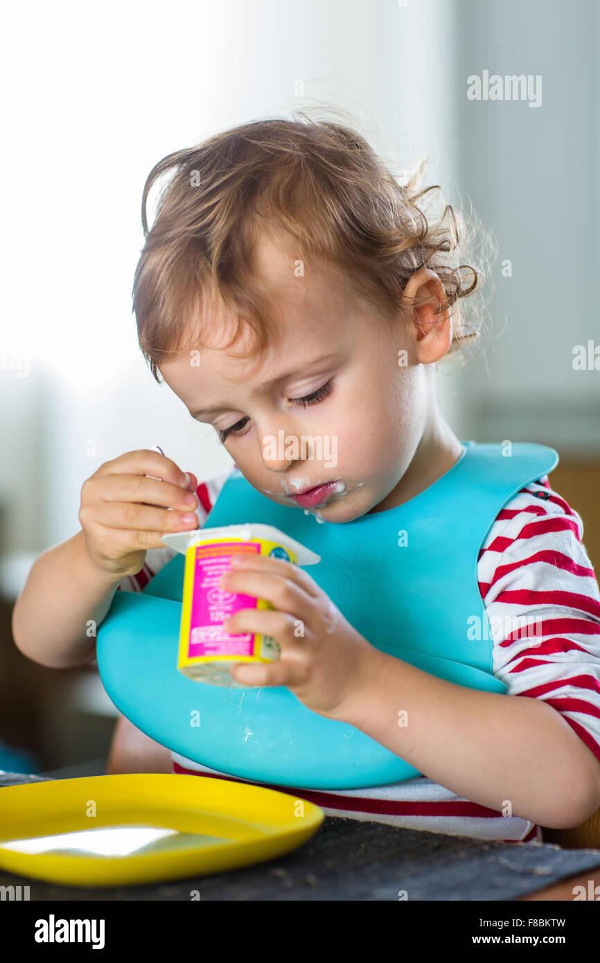 2 ans de manger un yaourt. Photo Stock