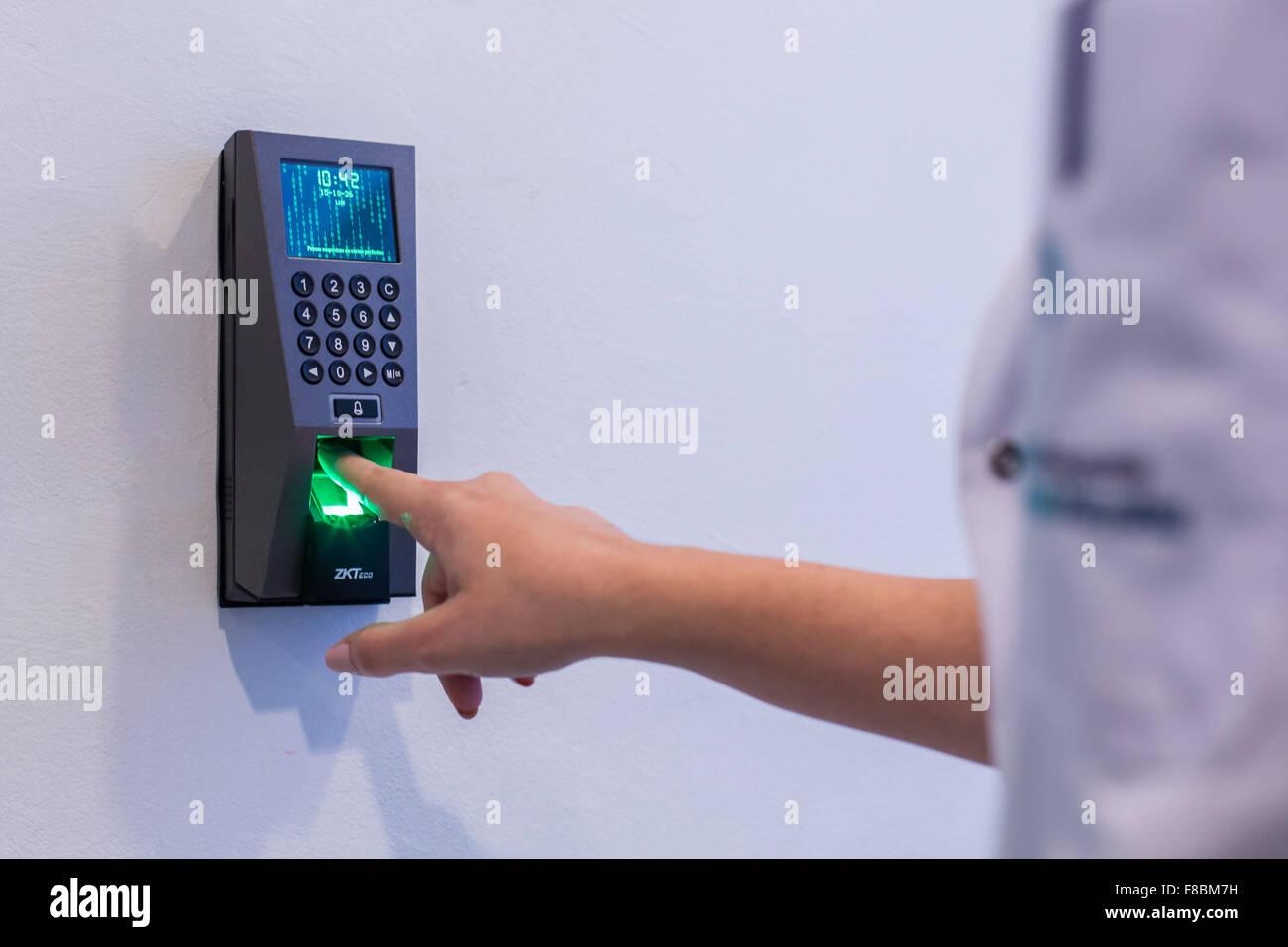 Infirmière au doigt numérisé par un scanner d'empreintes digitales. Photo Stock