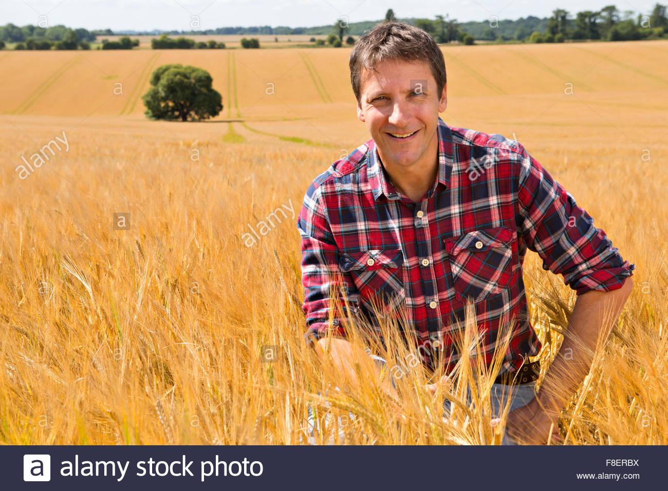 Portrait smiling farmer dans la récolte d'orge rural ensoleillée en été sur le terrain Photo Stock
