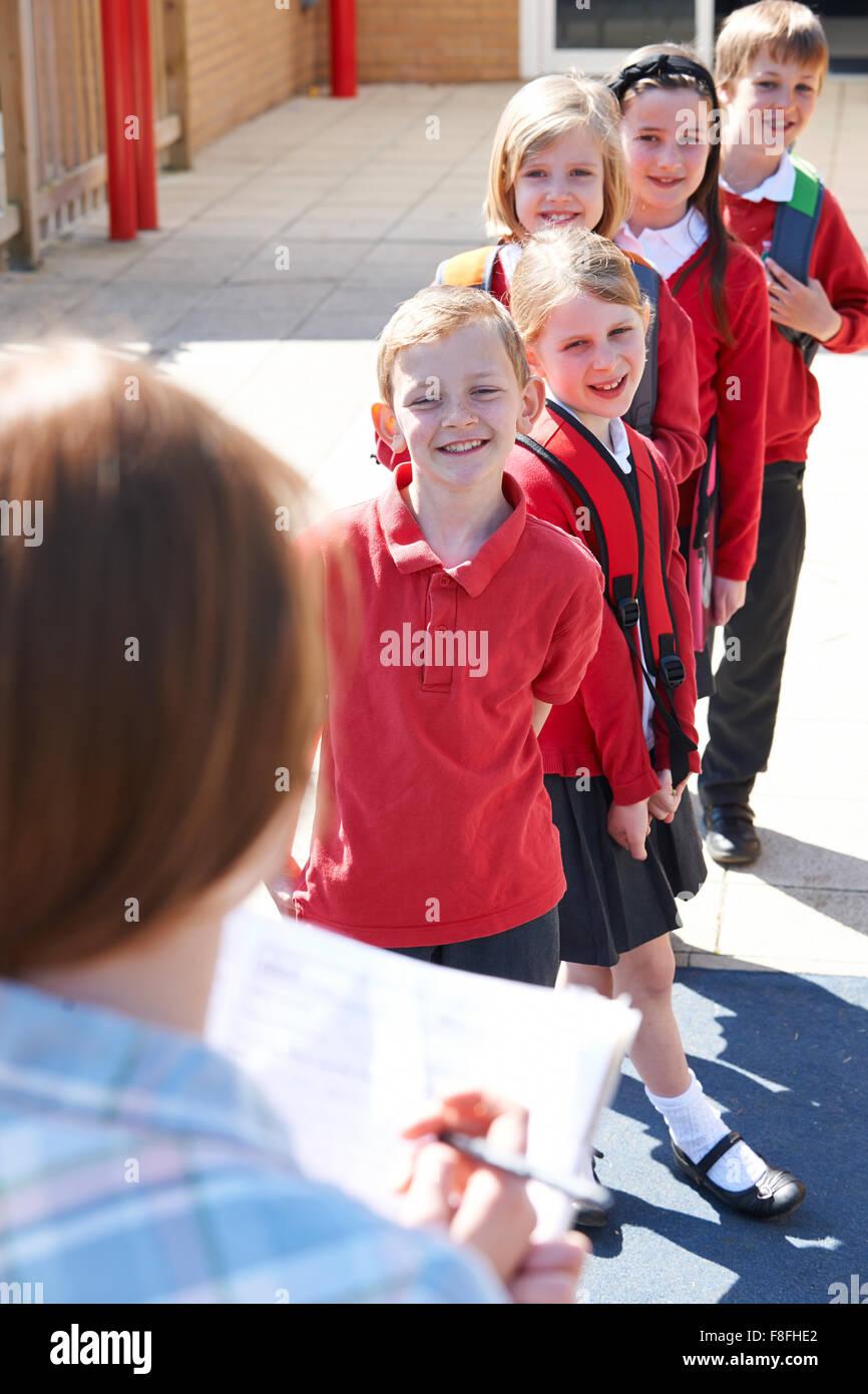 S'inscrire à l'école enseignant en tenant jeux pour enfants Photo Stock