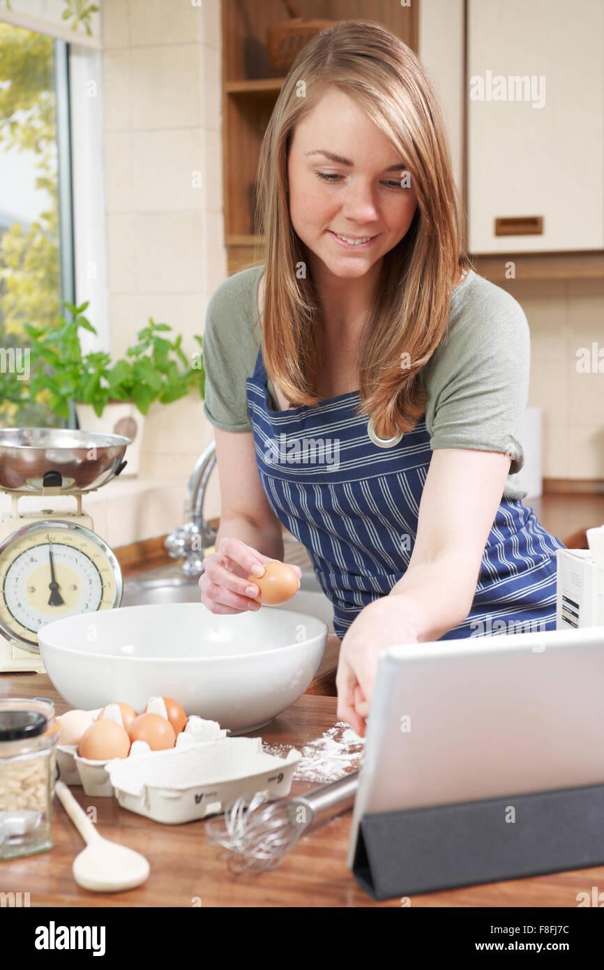 Woman Baking et recette suivante on Digital Tablet Photo Stock