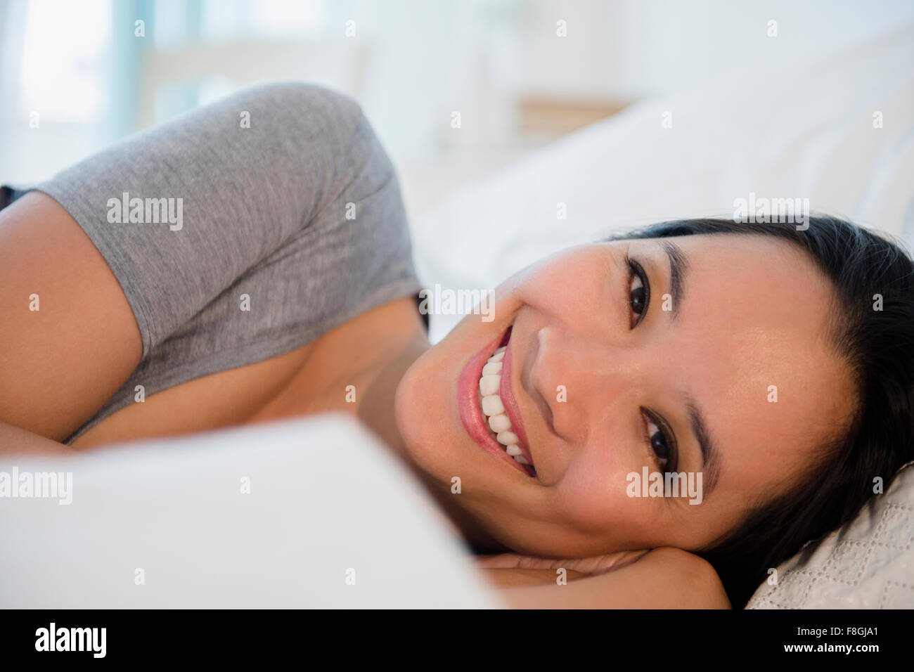 Chinese woman laying on bed Banque D'Images