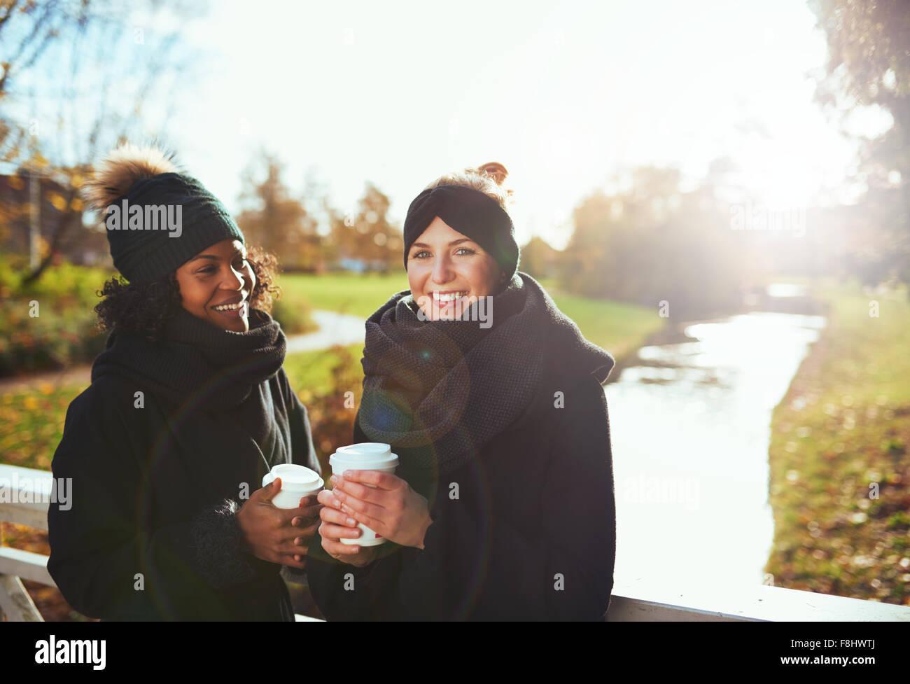 Deux copines à la caméra et à sourire en se tenant sur le pont, holding coffee to go, l'arrière Photo Stock
