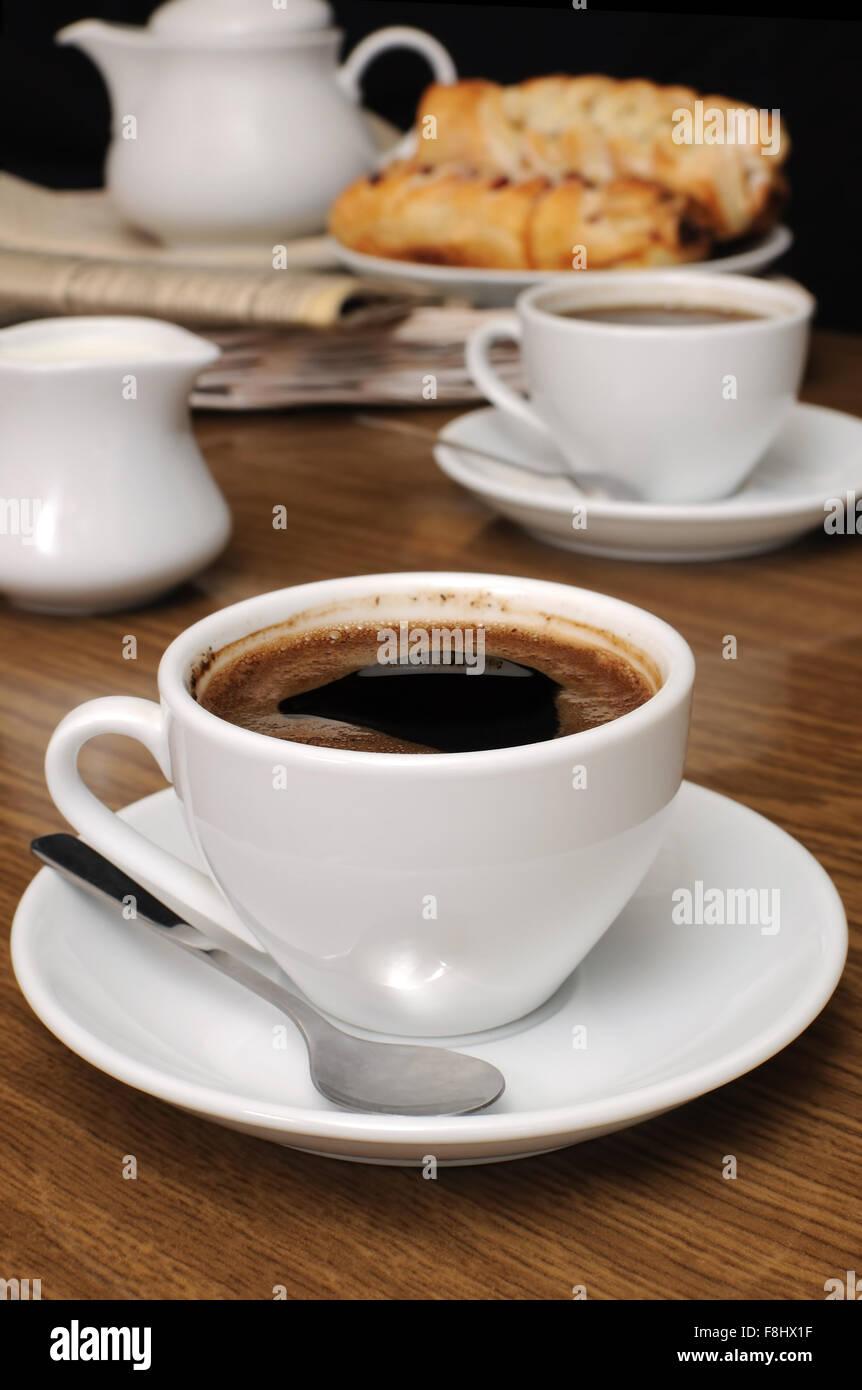 Tasse de café noir sur la table avec le laitier et les biscuits sur un plateau avec du papier journal Banque D'Images