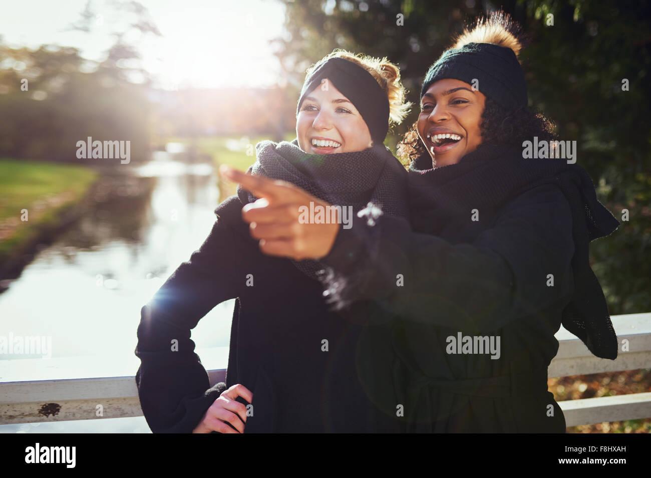 Deux copines de rire de quelque chose alors qu'il se trouvait dans le parc contre de rivière. Photo Stock