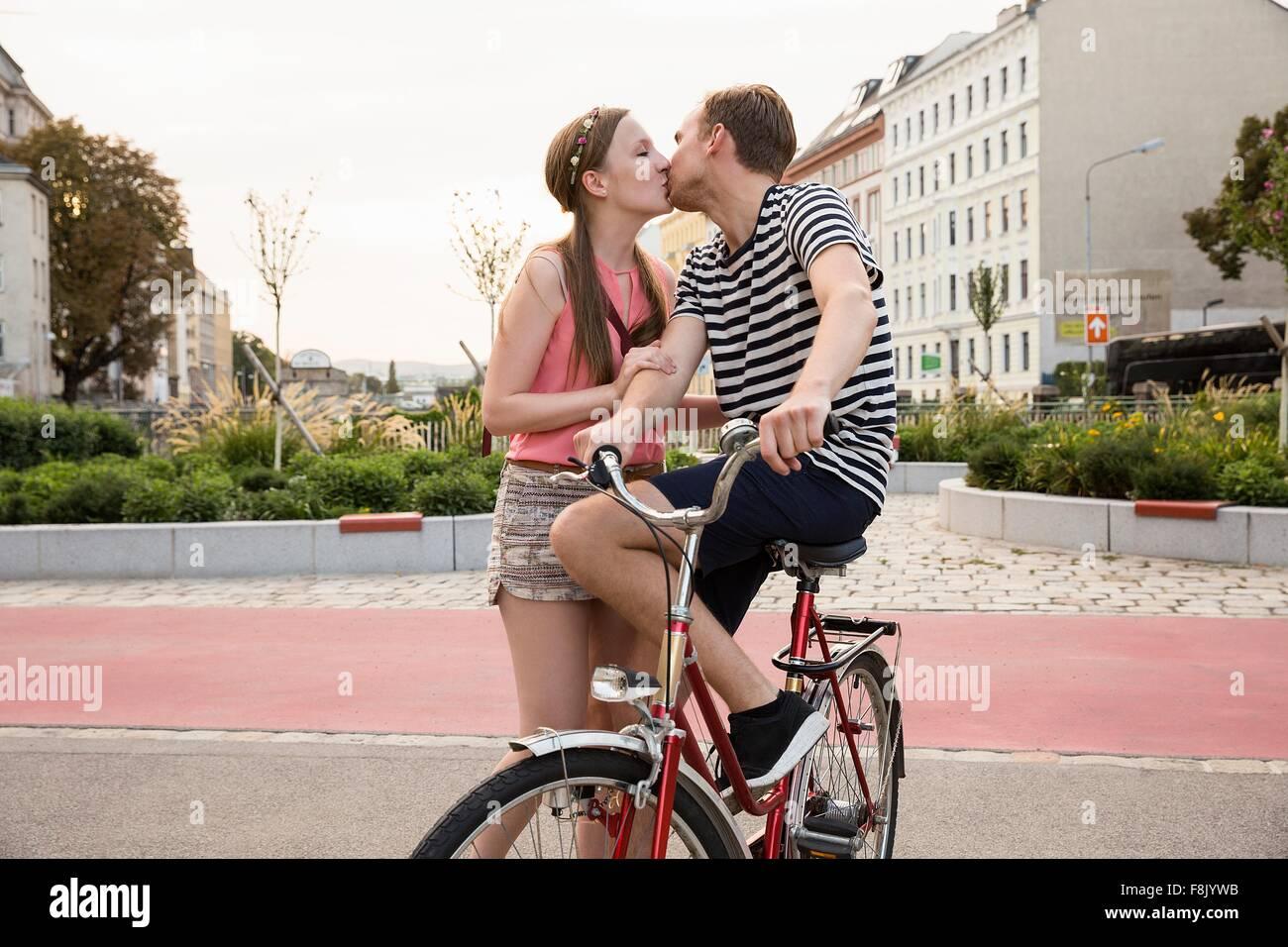Jeune homme assis sur sa bicyclette kissing young woman Banque D'Images