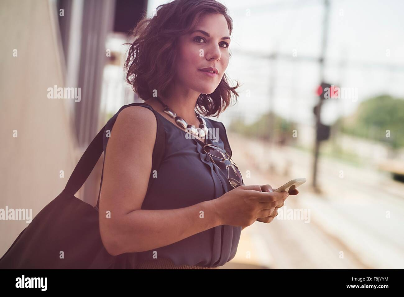 Mid adult woman en attente à la gare, holding smartphone Photo Stock