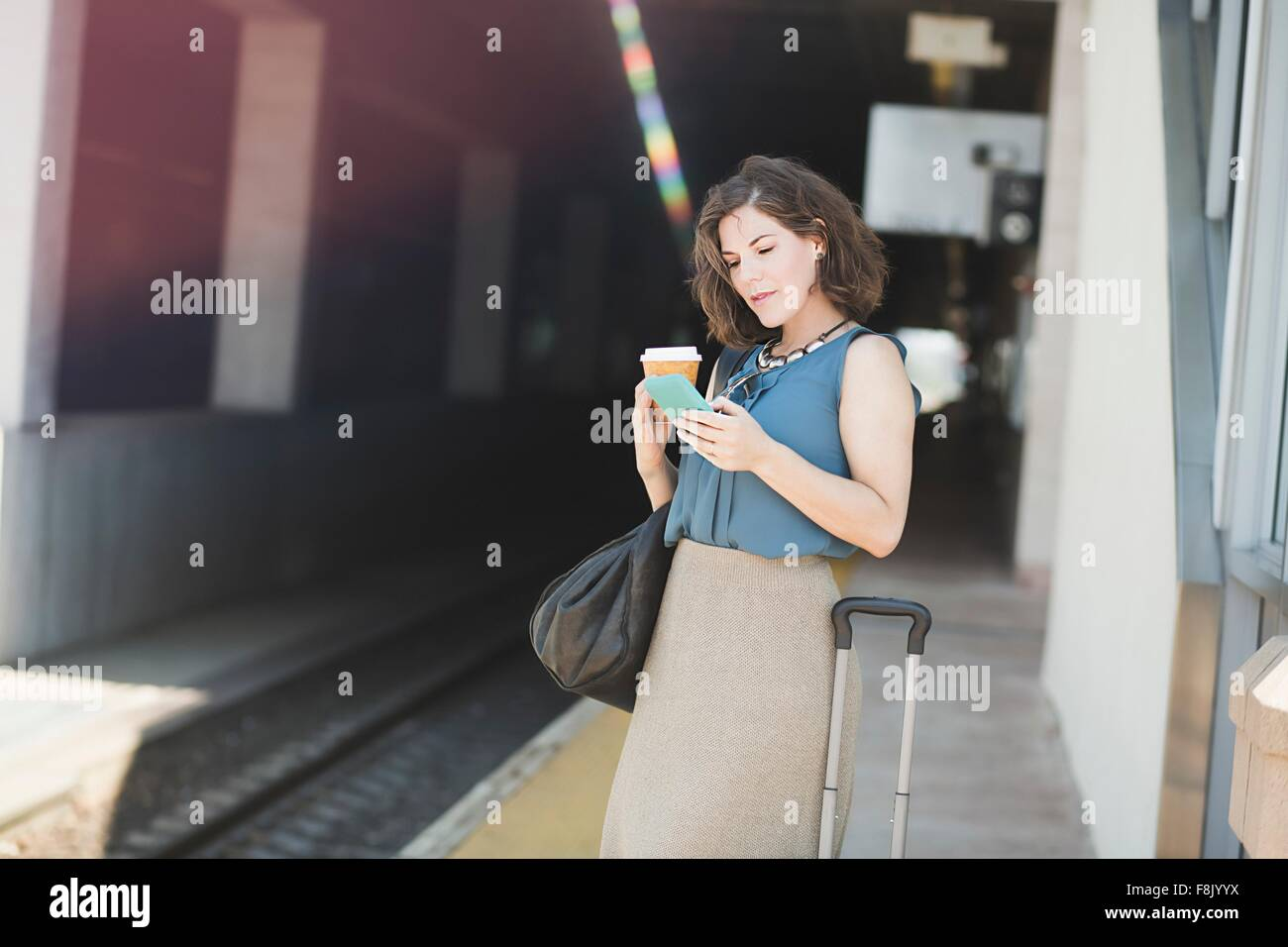 Mid adult woman en attente à la gare, l'utilisation de smartphone, holding Coffee cup Photo Stock