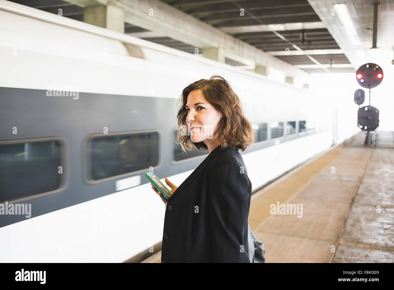 Mid adult woman en attendant l'embarquement, la holding smartphone Photo Stock