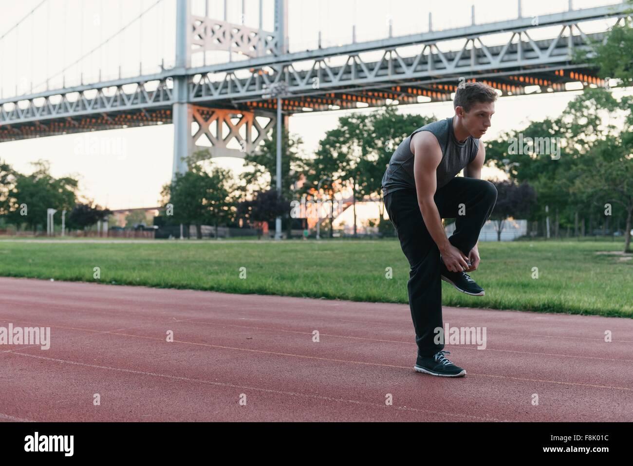Jeune homme debout sur la voie des sports, lacet de liage Photo Stock