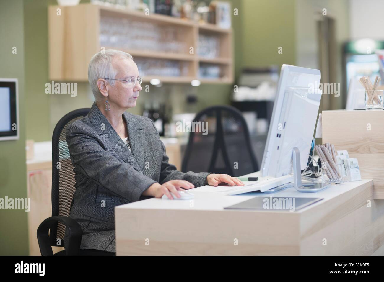 Réceptionniste femme senior à l aide d ordinateur de bureau à la