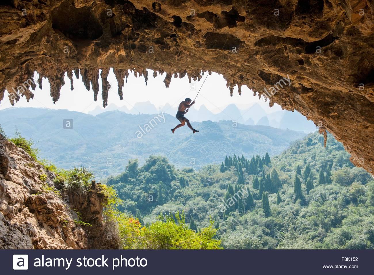 Grimpeur mâle prenant une chute à Odin's Den à côté de Moon Hill dans Yangshuo, Guangxi Photo Stock