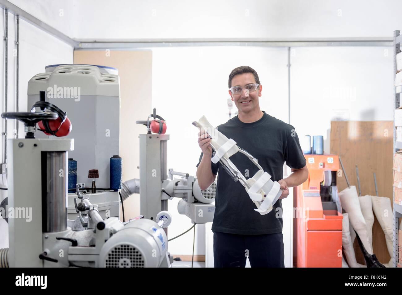 Worker holding support orthopédique médical en usine, portrait Photo Stock