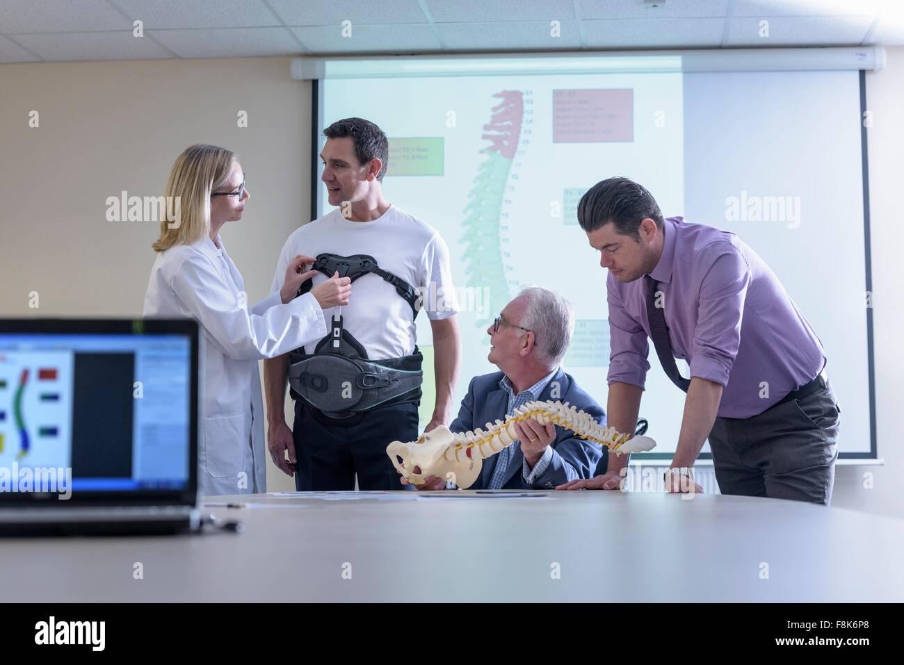 Réunion des concepteurs en discuter back support orthopédique Photo Stock