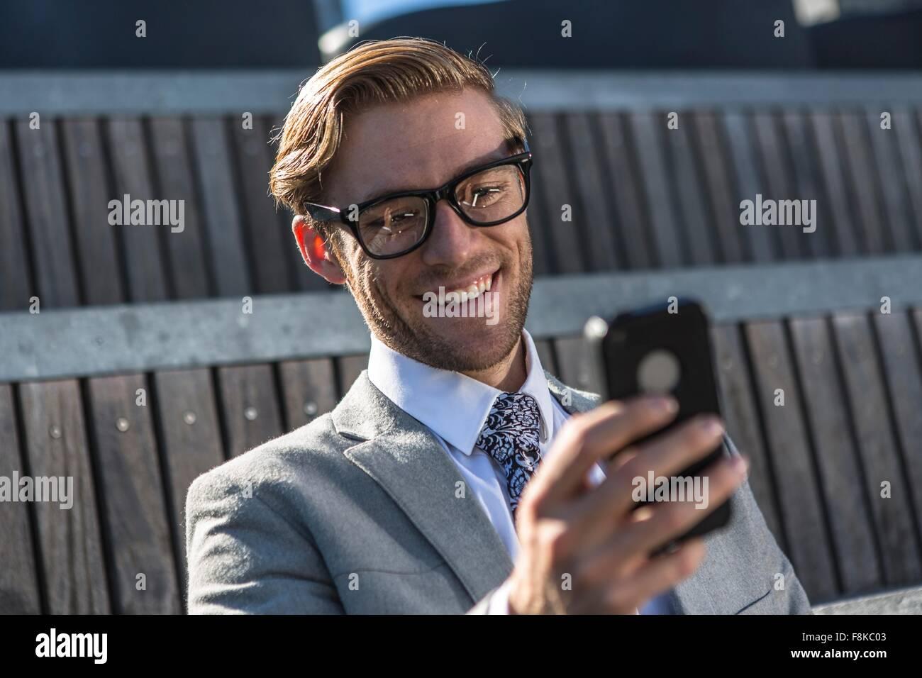 Young businessman reading text smartphone en ville Banque D'Images