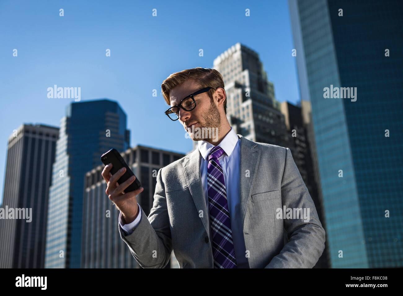 Jeune homme d'en face du bâtiment de bureaux lecture textes smartphone, New York, USA Photo Stock