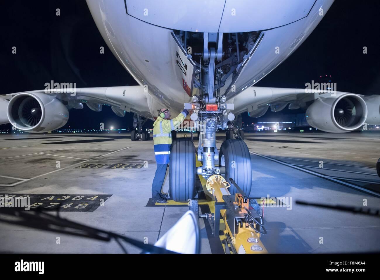 Ingénieur en chef de l'inspection d'A380 sur la piste à l'aéroport de nuit Photo Stock