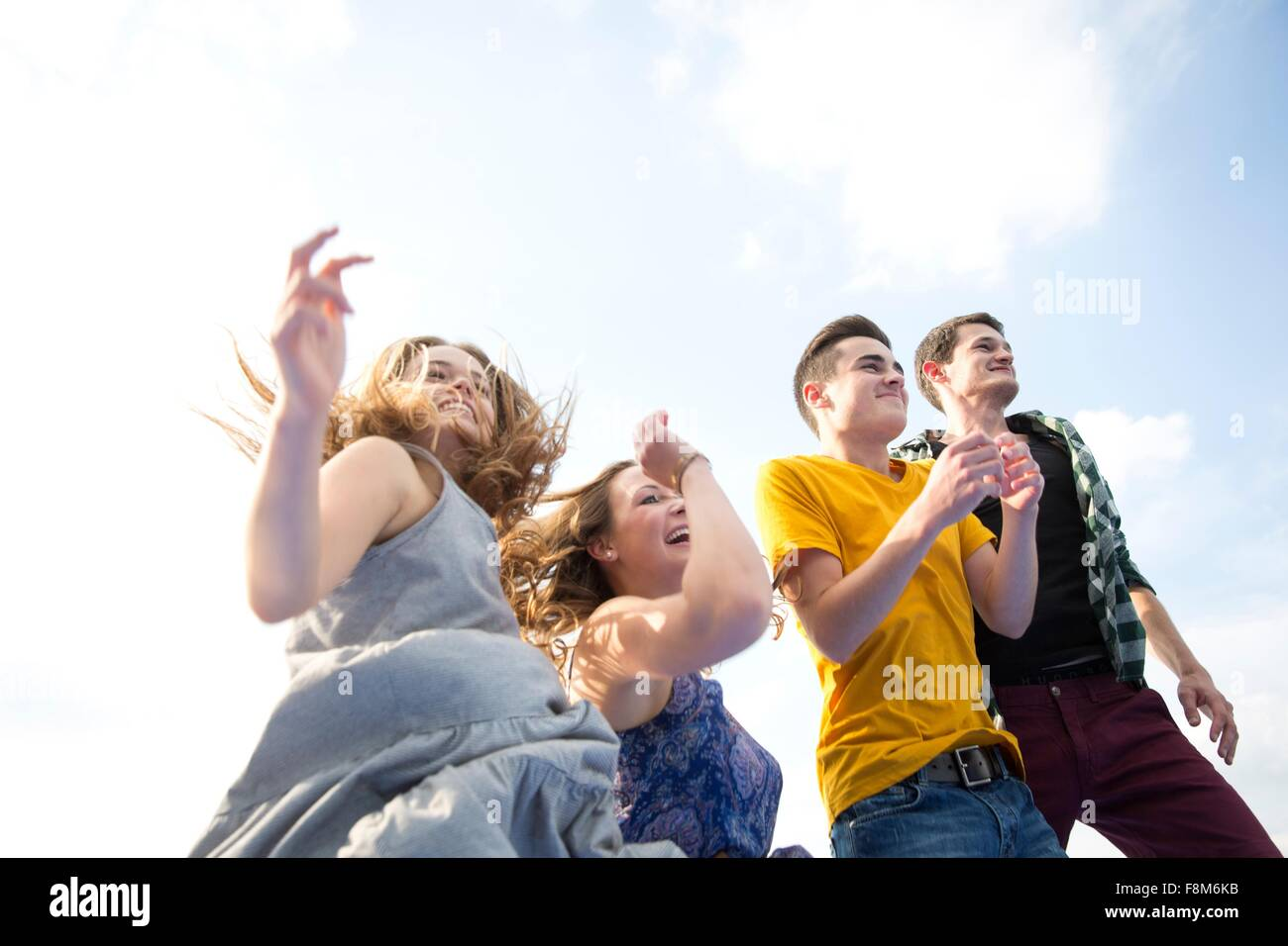 Groupe de jeunes adultes, d'exécution, à l'extérieur, low angle view Photo Stock