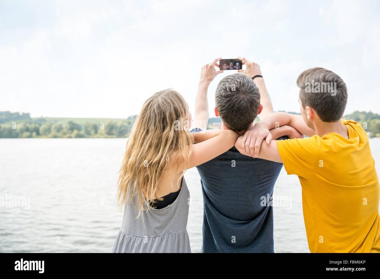 Trois jeunes adultes taking self portrait en utilisant smartphone, vue arrière Photo Stock