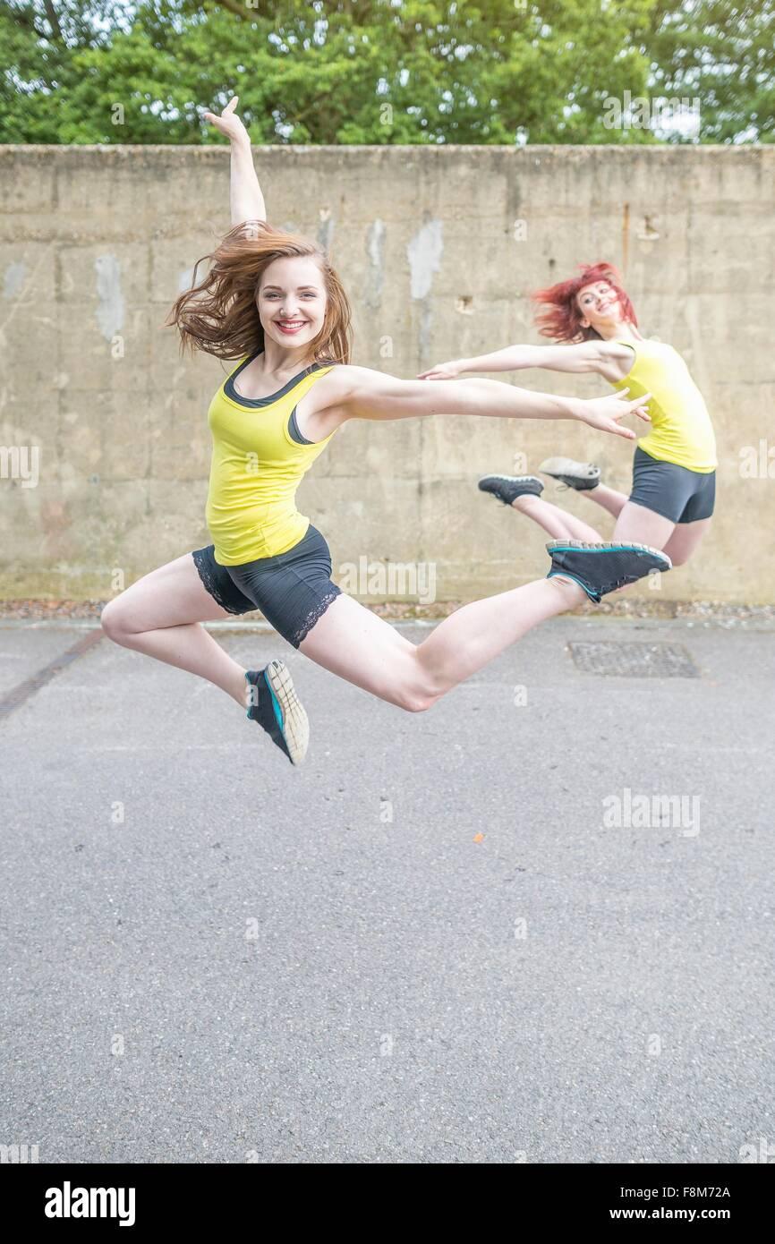 Les jeunes femmes de sauter devant un mur de béton Photo Stock