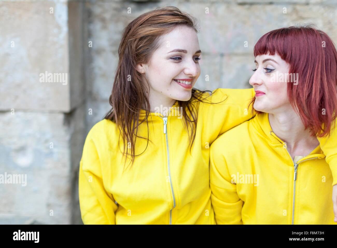 Young women smiling, mur en pierre en arrière-plan Photo Stock