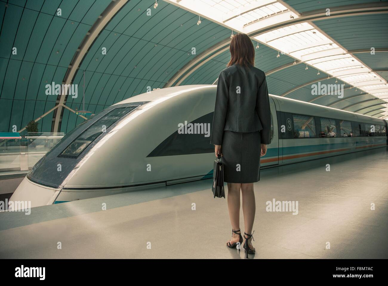 Femme d'affaires en attente d'un train sur un quai de gare, Shanghai, Chine Photo Stock