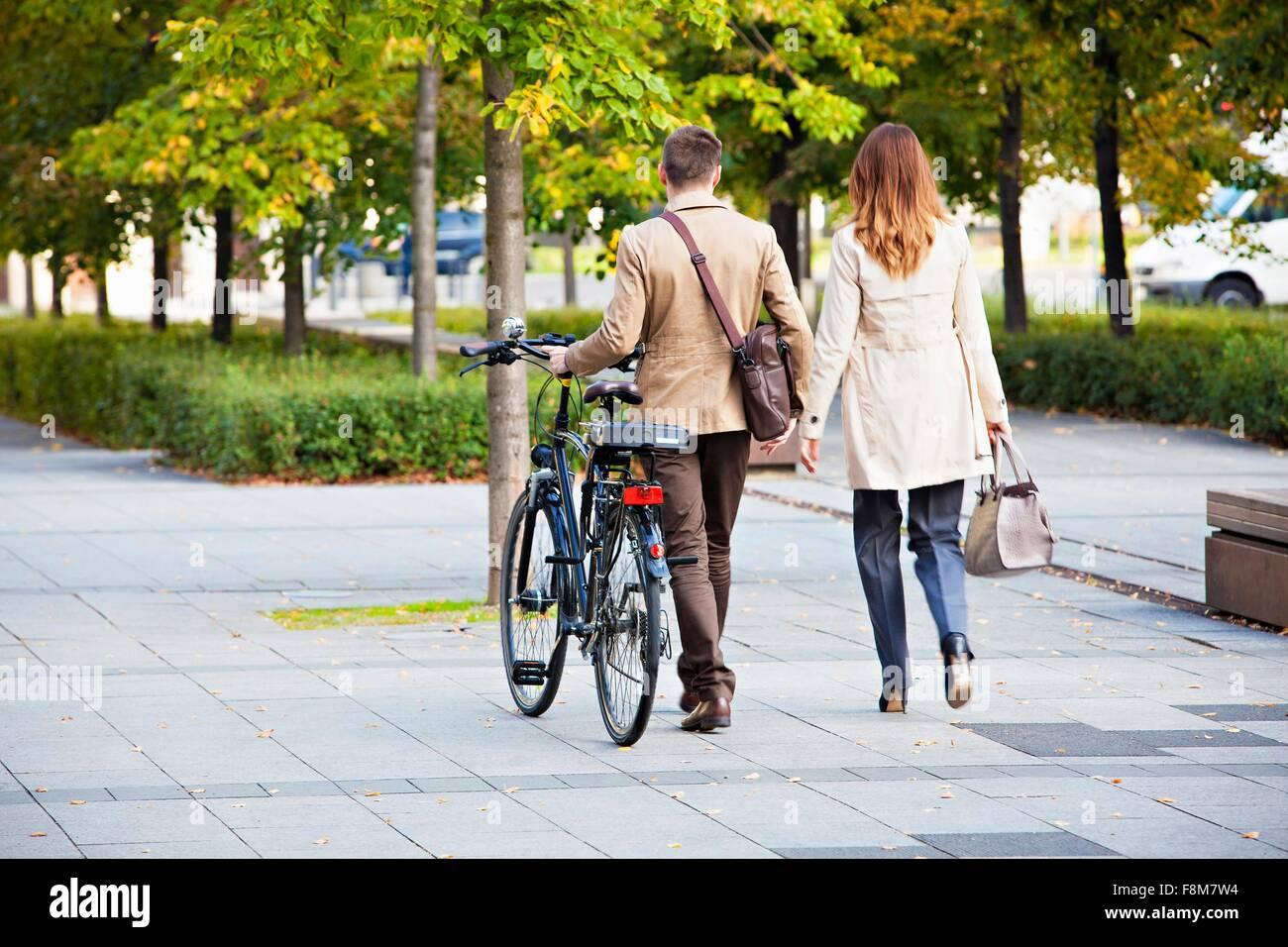 Businessman et woman pushing bike Banque D'Images