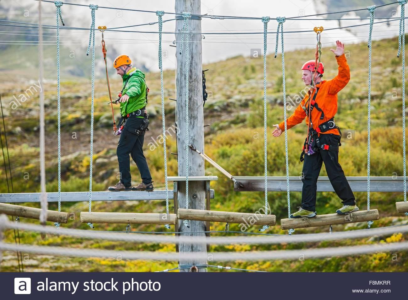 L'équilibre entre les hommes à des cours accès sur corde, l'Islande Photo Stock