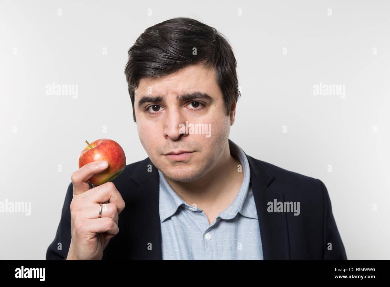 Dark-haired'businesmann avec un regard sérieux tenir une petite pomme alors qu'en face d'un gradient Photo Stock
