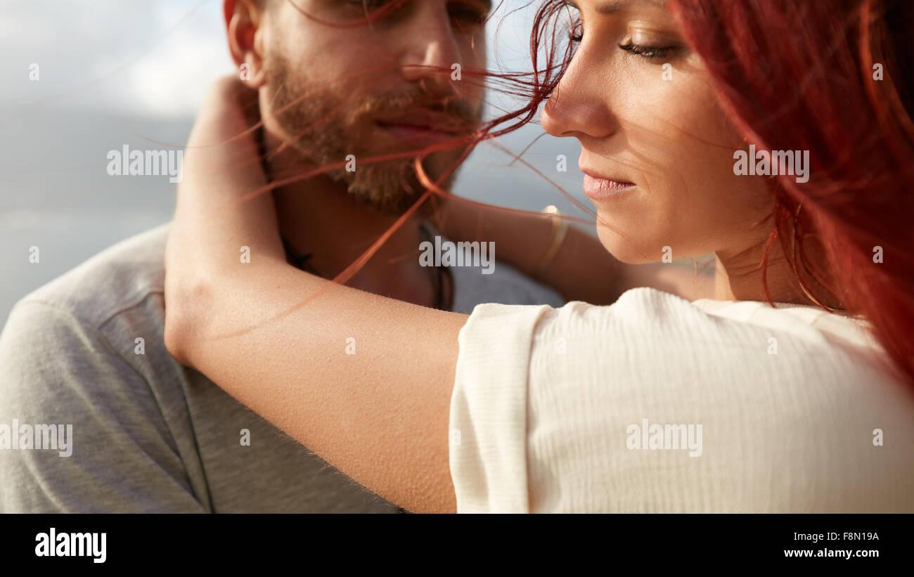Gros plan de jeune femme avec son petit ami à l'extérieur. Jeune couple en vacances. Photo Stock