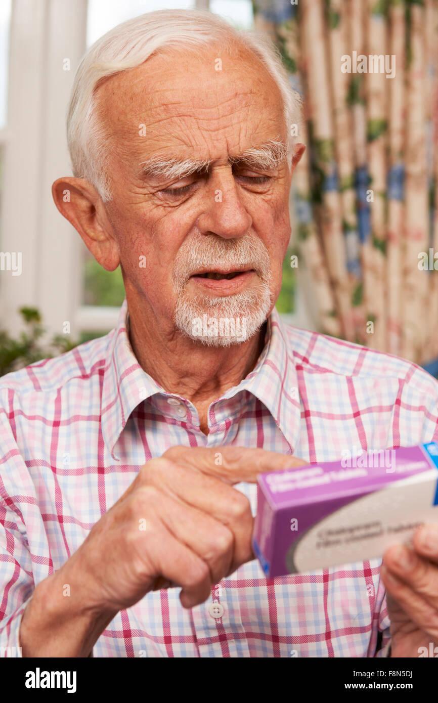 Senior Man reading Instructions sur le médicament Photo Stock