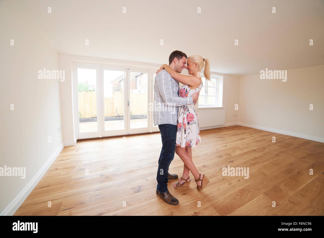 Jeune couple excité en salle vide de leur première maison Photo Stock