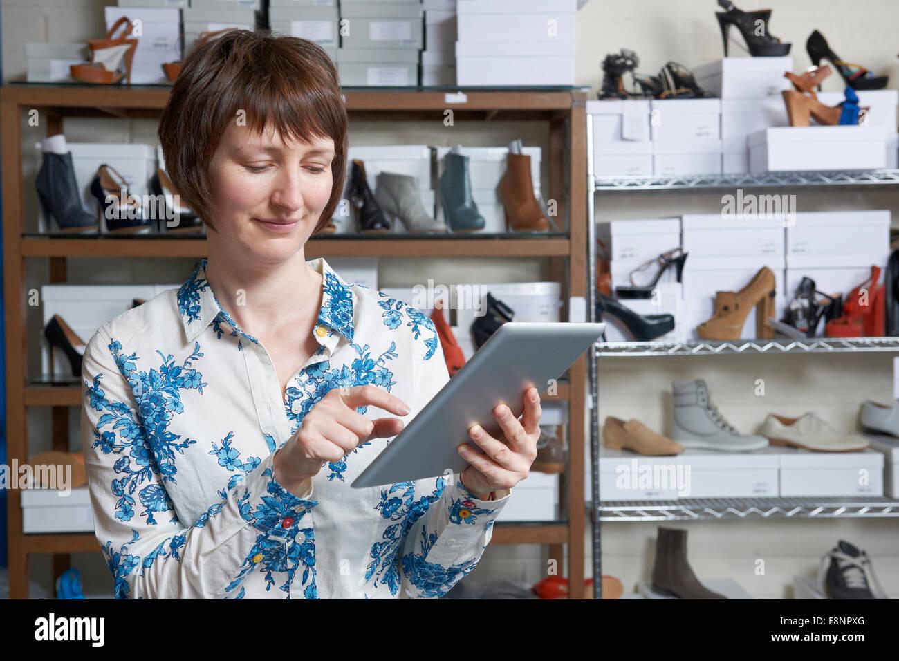 Propriétaire d'entreprise de chaussures en ligne using digital Tablet Photo Stock
