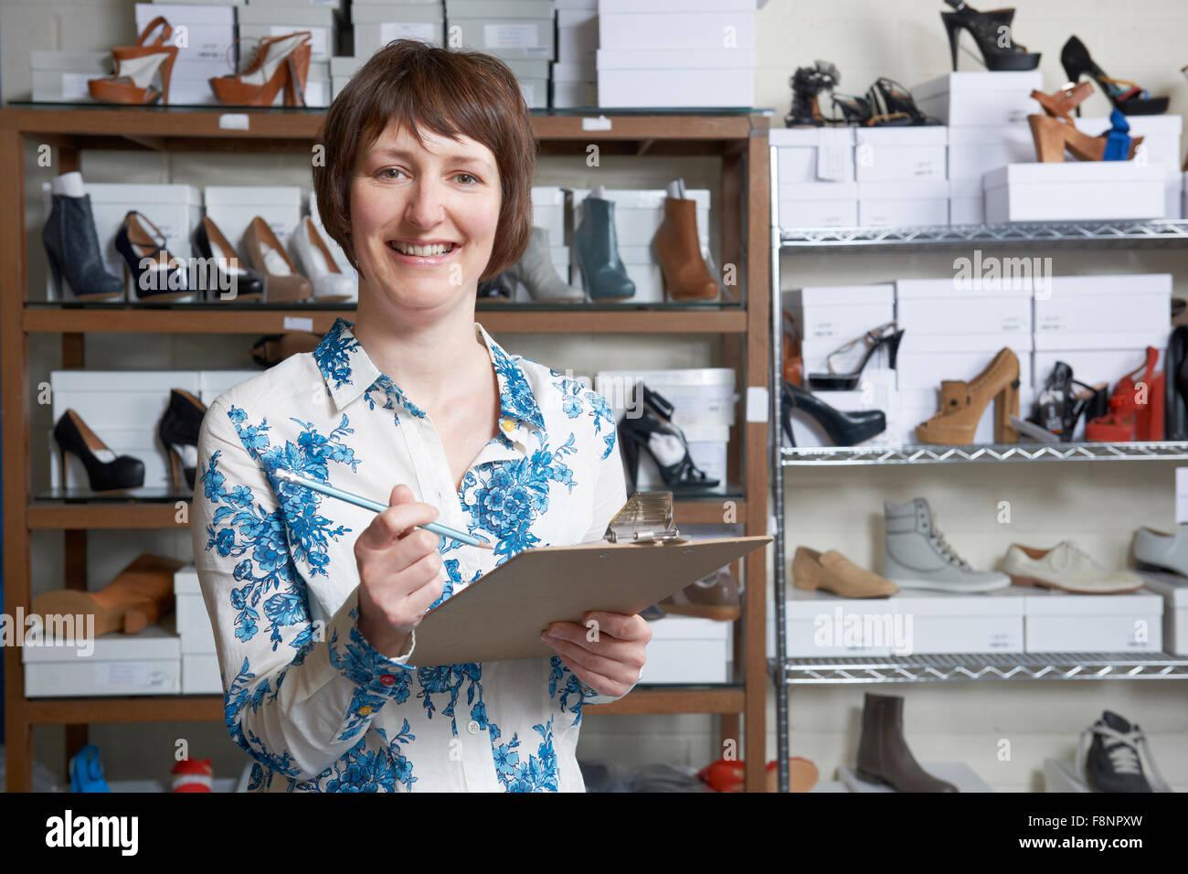 Femme propriétaire d'entreprise de chaussures en ligne avec presse-papiers Photo Stock