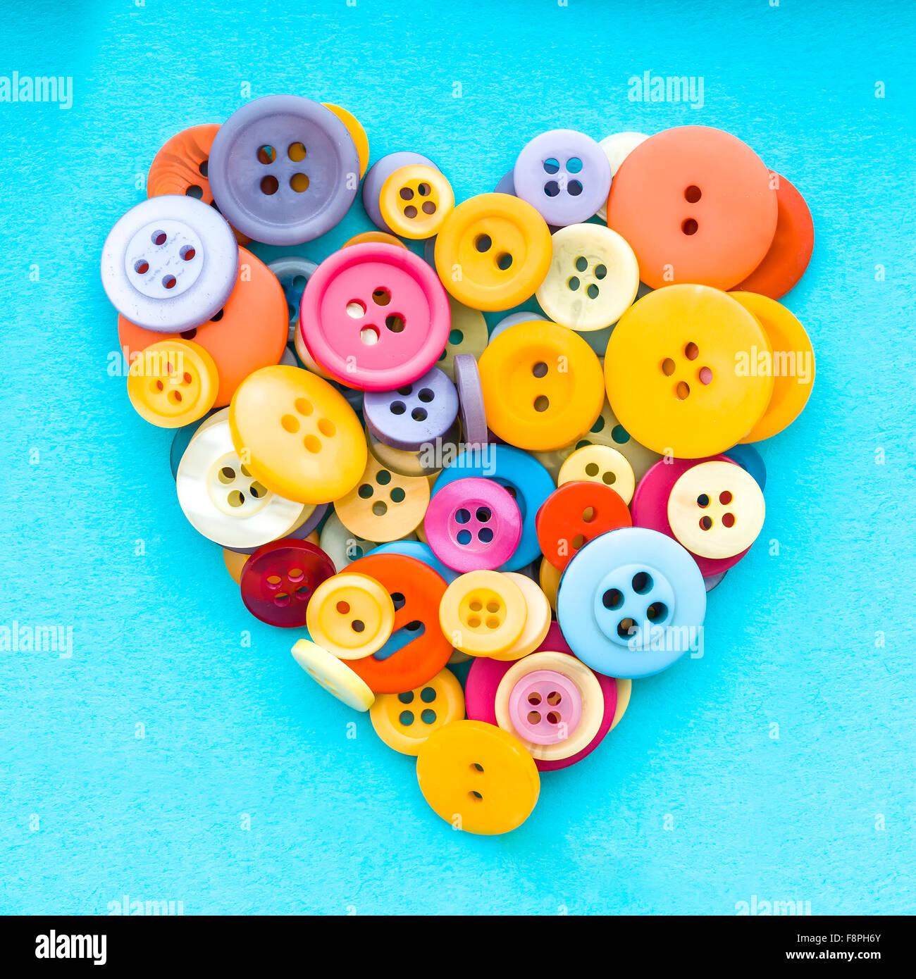 Les boutons colorés en forme de cœur sur un rétro arrière Photo Stock