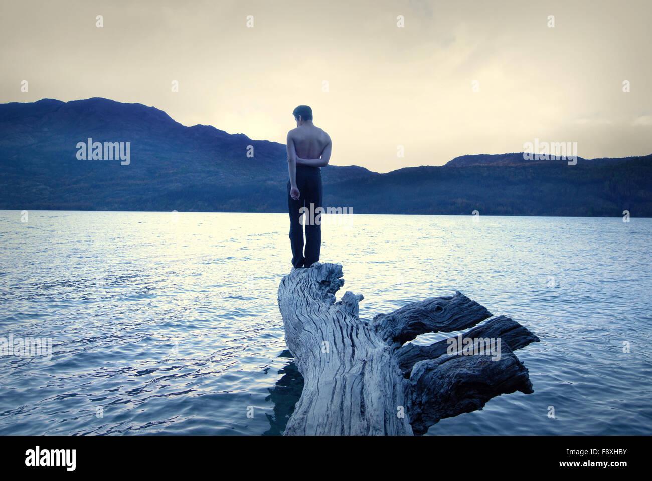 Garçon debout dans un arbre tombé au milieu de l'eau, ciel d'orage, vintage et conceptuel Banque D'Images
