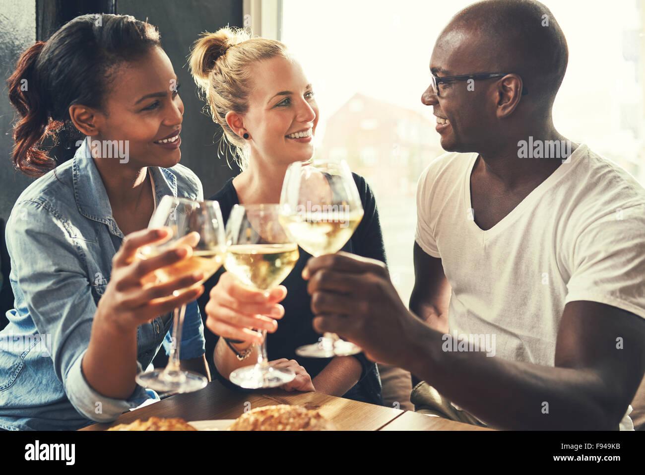 Amis ethniques dans un bar boire du vin et manger des tapas Photo Stock