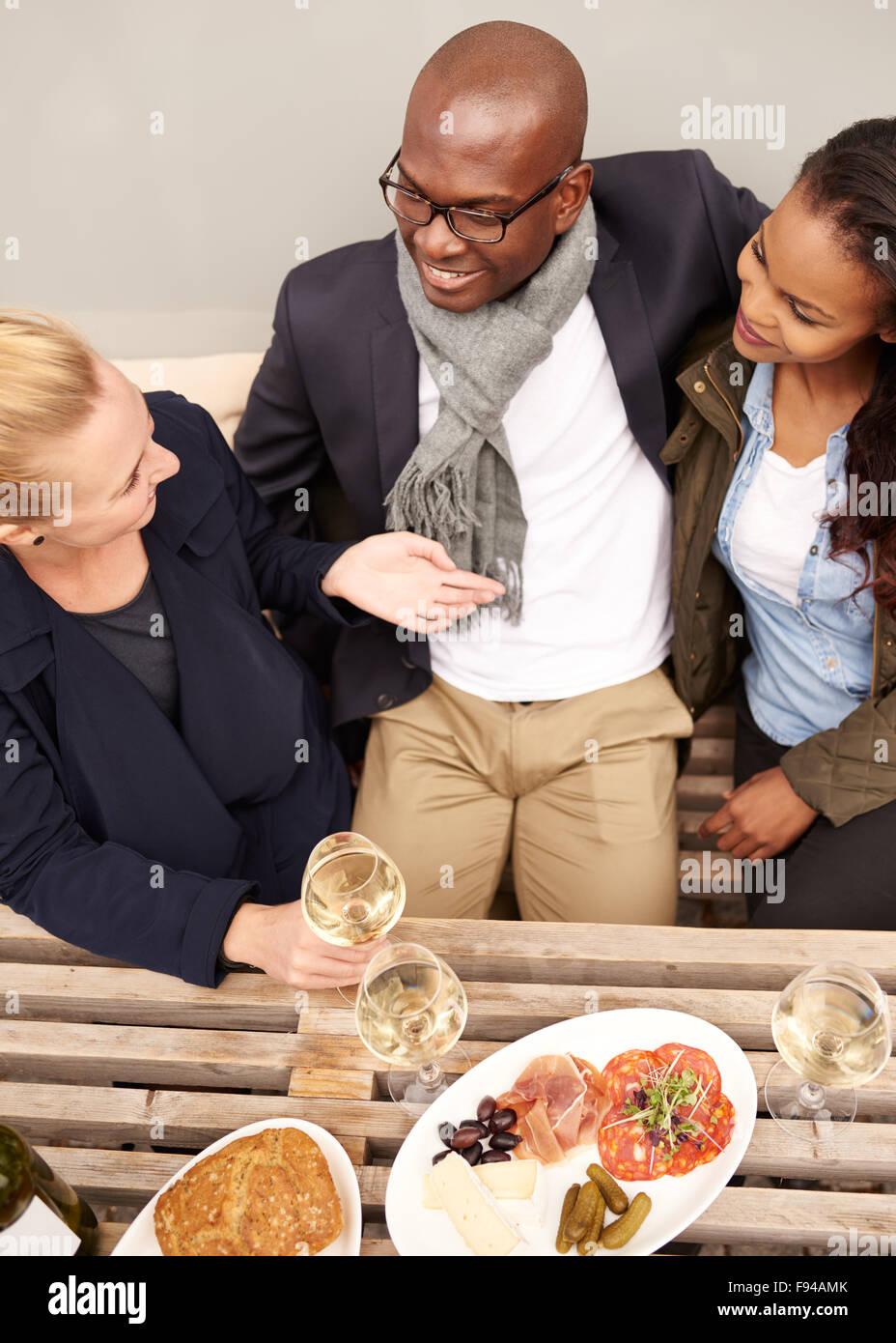 Groupe d'amis en train de dîner à l'extérieur, multi ethnie Photo Stock