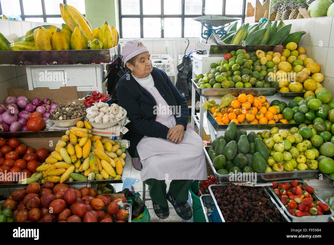 Quito , en Équateur. Le Mercado Central de Quito. Une femme dort sur son étal de fruits. Photo Stock