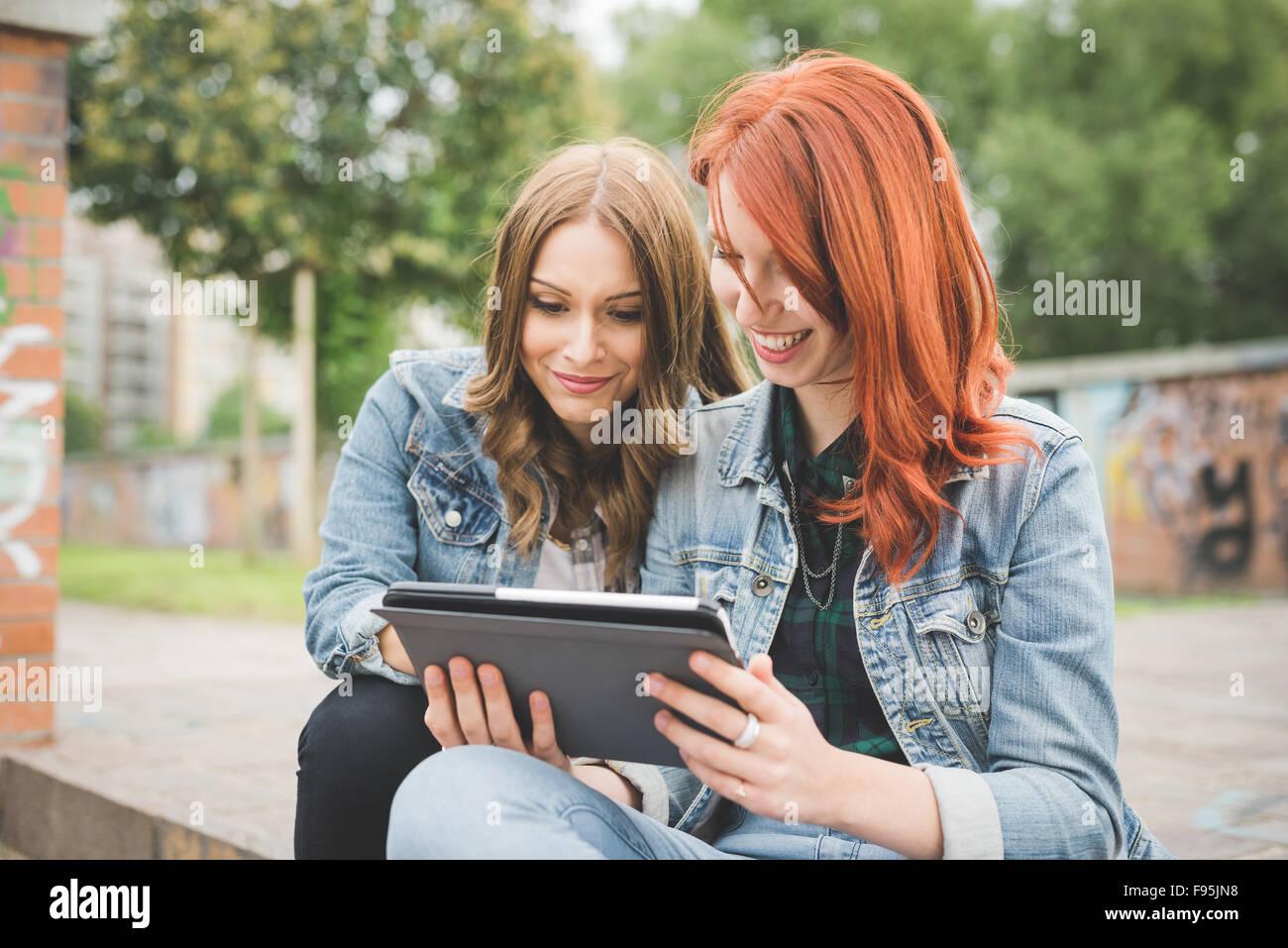 La moitié de la longueur de deux jeunes handsome young Blonde Redhead et les cheveux droits femmes assis sur Photo Stock
