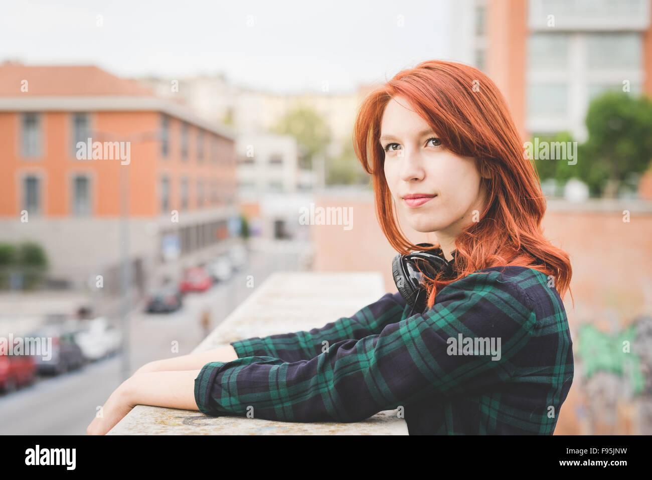 Demi-longueur de jeunes beau portrait rousse les cheveux droits femme appuyée sur une main courante, donnant Photo Stock