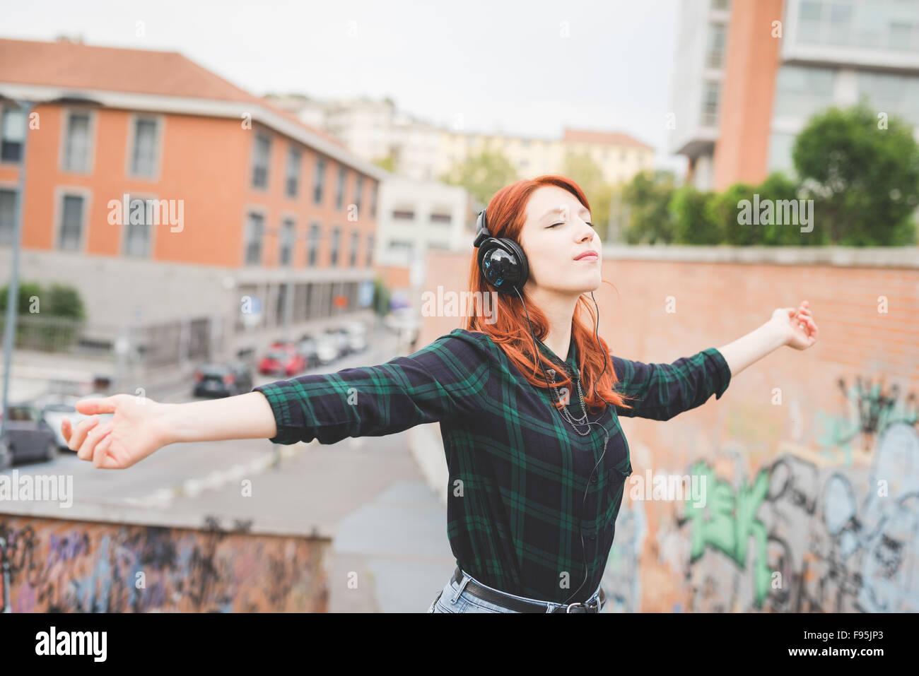 Demi-longueur de jeunes beau portrait rousse les cheveux droits woman listening music avec casque, se sentir libre Photo Stock