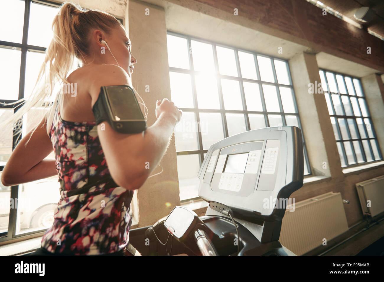 Les jeunes femmes ciblées l'élaboration à la salle de sport le jogging sur un tapis roulant. Photo Stock