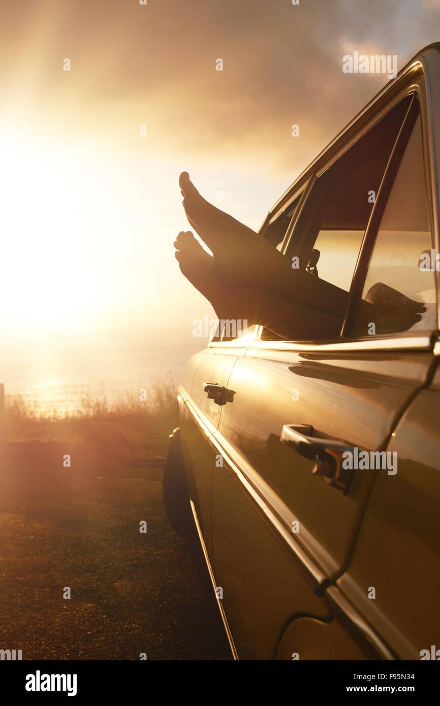 Vacances d'concept de voyage routier. Woman hanging ses jambes hors de la fenêtre de voiture au coucher Photo Stock
