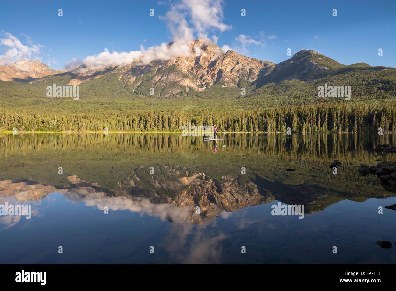 Reflet de la montagne Pyramid et femme paddle sur le lac Pyramid. Le Parc National Jasper, Alberta, Canada. Photo Stock