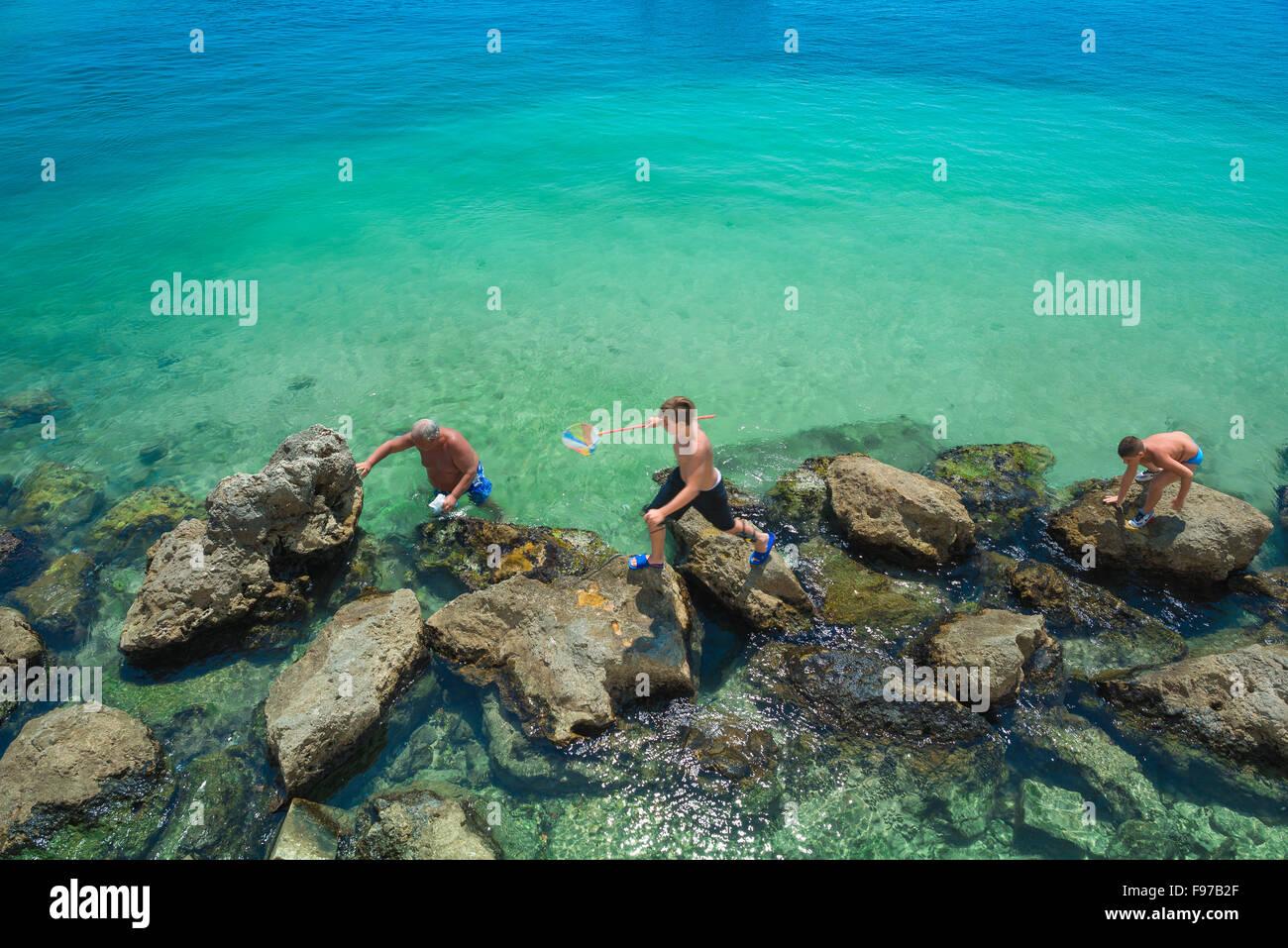 Rock La famille piscine, vue d'un groupe familial de pêche dans une roche couverte par un après-midi Photo Stock