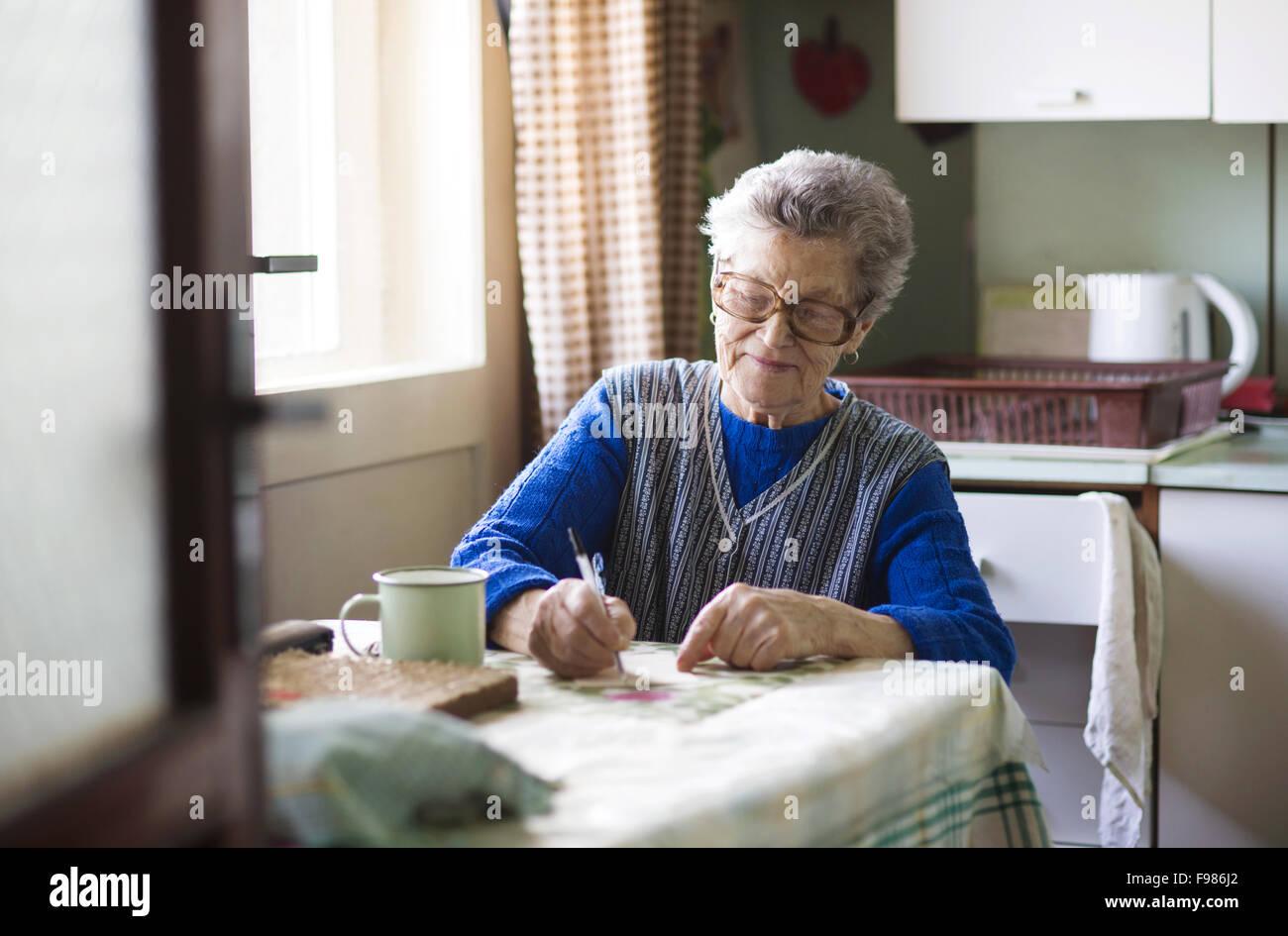 Vieille Femme est assise dans sa cuisine de style campagnard Photo Stock