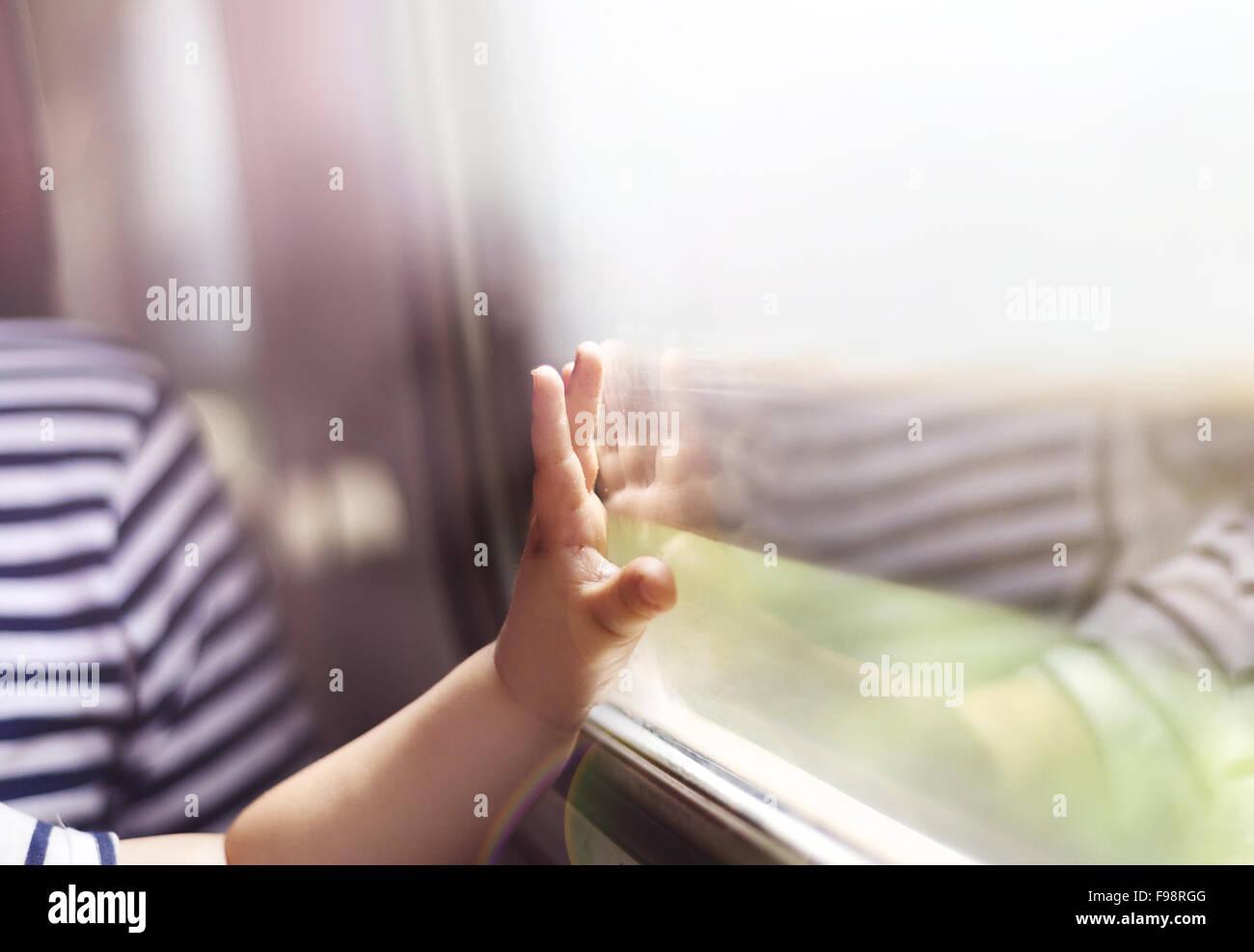 Garçon voyageant en train rétro. Il est en contact avec la fenêtre. Photo Stock