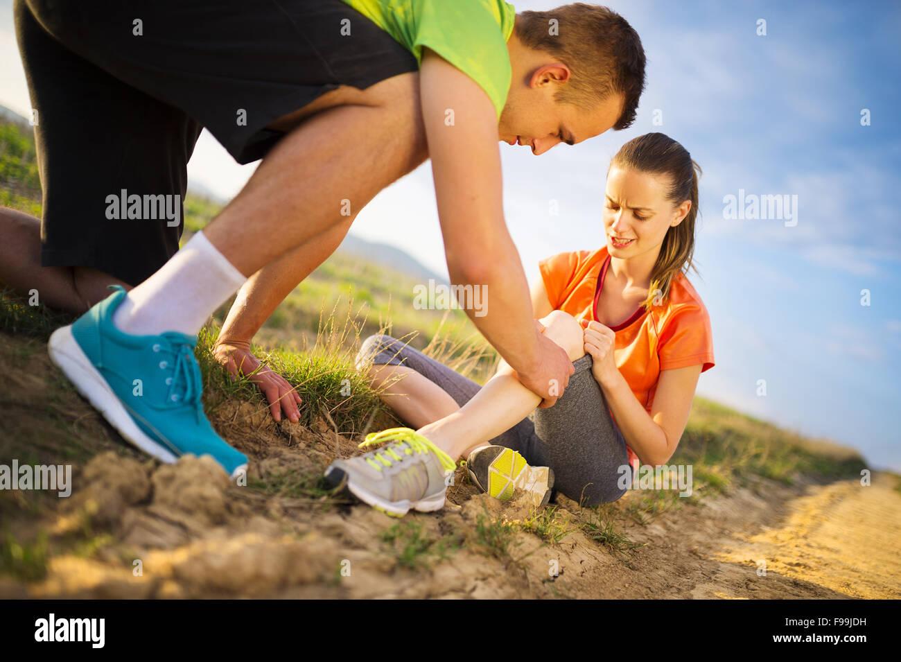 Dommage - sport femme avec genou blessé obtenez de l'aide de l'homme de toucher son genou. Photo Stock