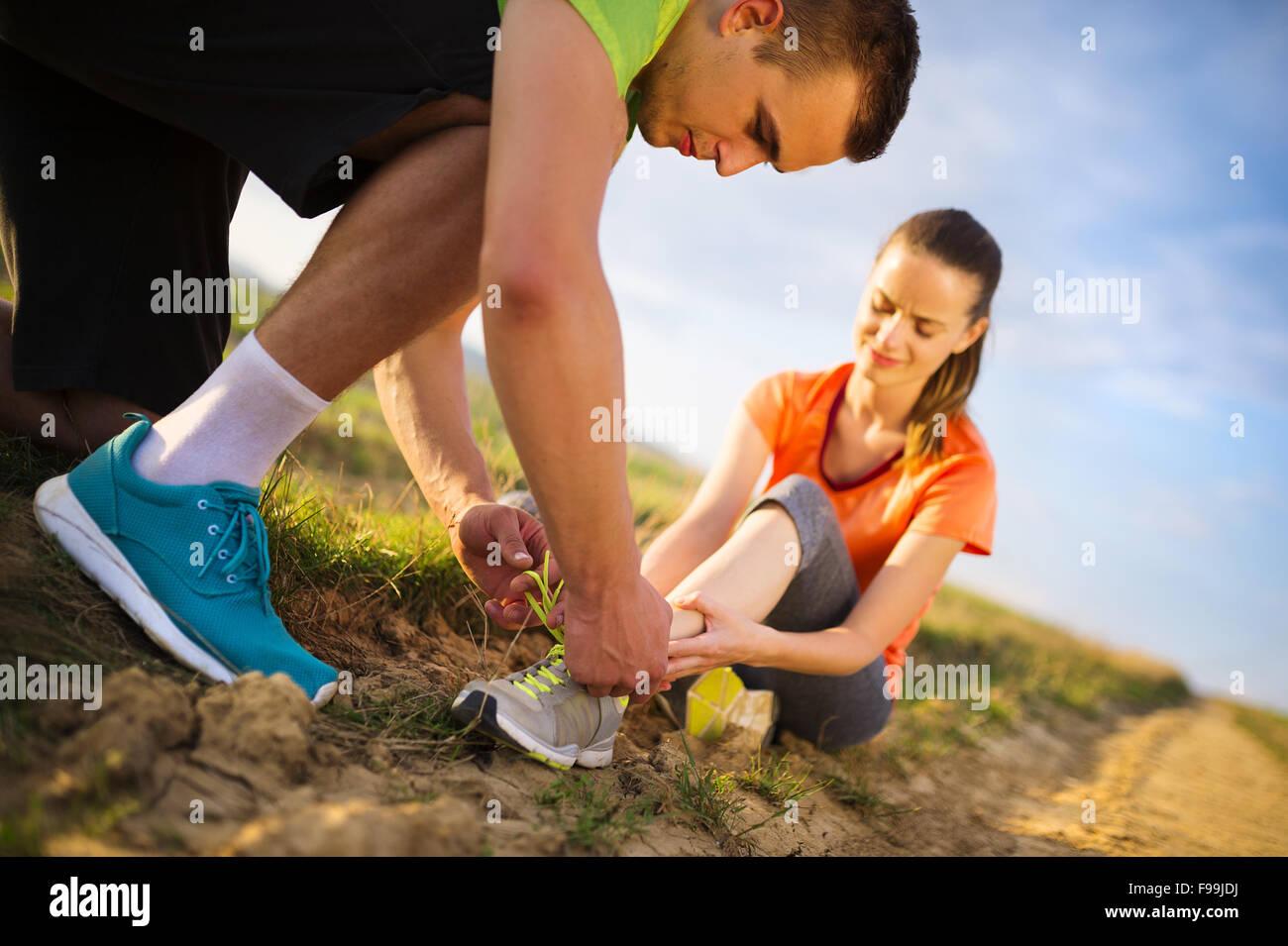 Dommage - sport femme avec twisted entorse obtenez de l'aide de l'homme touchant la cheville. Banque D'Images